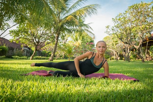 Vrouw die yoga in tuin doet