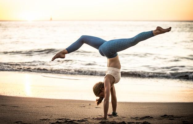 Vrouw die yoga maakt stelt op het strand