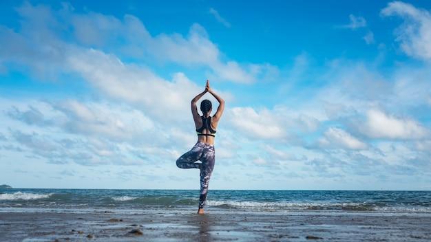 Vrouw die yoga-oefeningen op het strand in de ochtend.