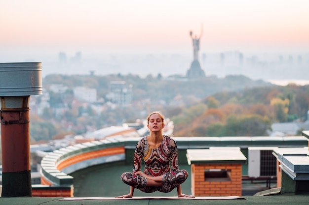 Vrouw die yoga op het dak van een wolkenkrabber in grote stad doet