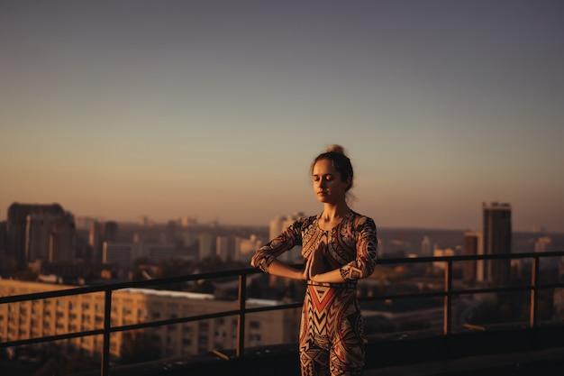 Vrouw die yoga op het dak van een wolkenkrabber in grote stad doet.