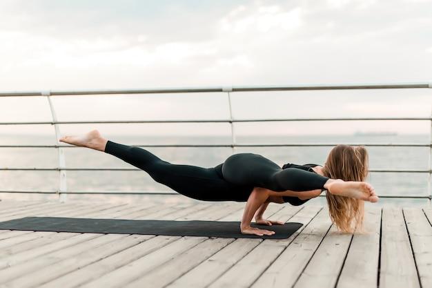 Vrouw die yoga op het strand doet en zich op haar handen bevindt