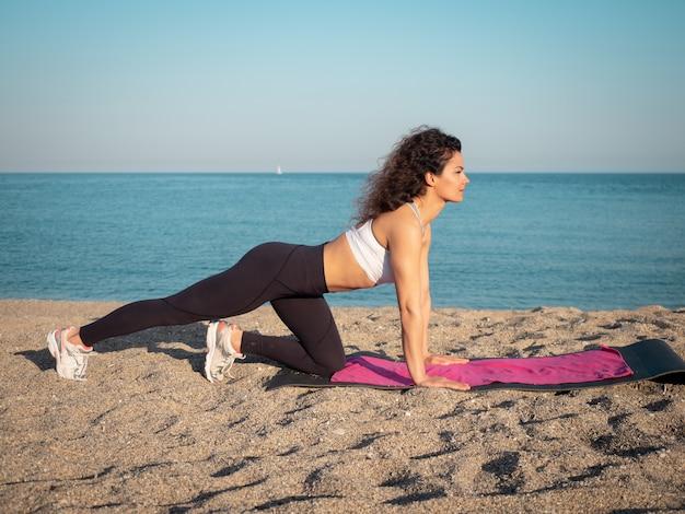 Vrouw die yoga op het strand doet