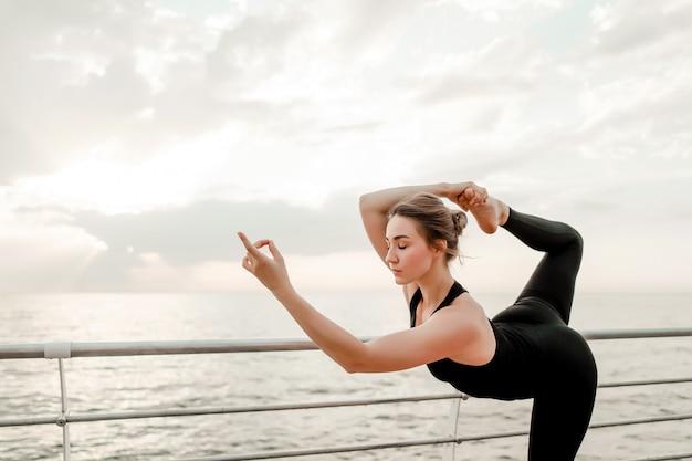 Vrouw die yoga op het strand in moeilijke asanapositie doet