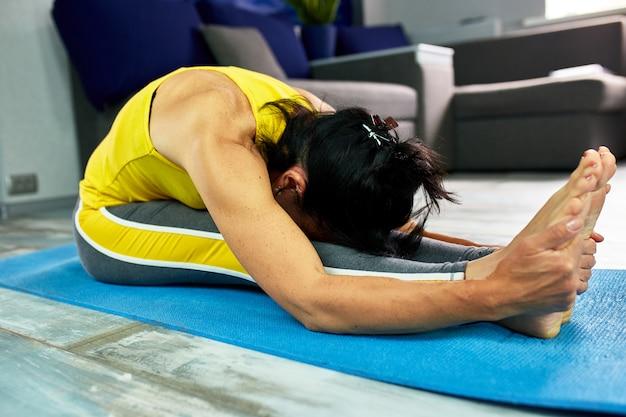 Vrouw die yoga thuis doet, rekoefeningen doet.