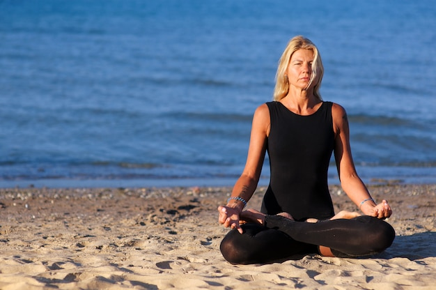 Vrouw die yogaasana doet bij het strand