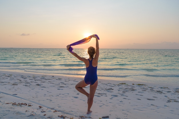 Vrouw die yogaoefening op de romantische hemel van het zandstrand uitvoert bij zonsondergang, achtermening, gouden zonlicht, echte mensen