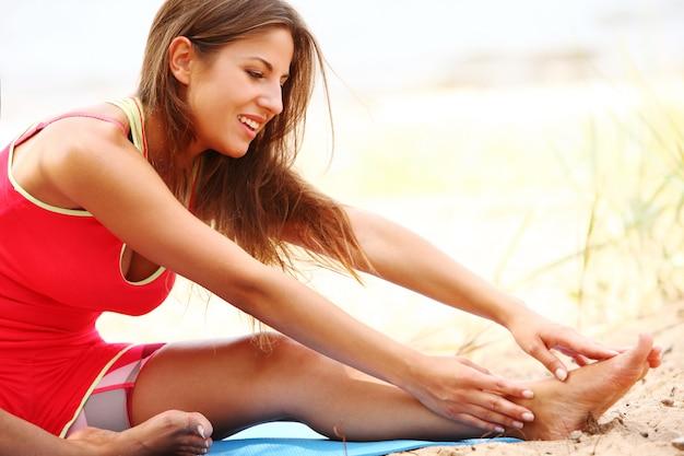 Vrouw die yogaoefeningen op de kust doet