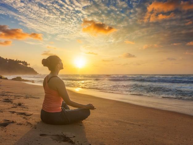 Vrouw die yogaoudoors doen bij strand - de padmasana-lotusbloem stelt