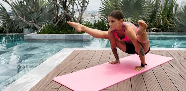 Vrouw die yogapositie beoefent bij het zwembad; buiten
