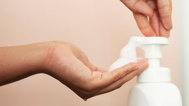 Vrouw die zeep gebruikt om handen te reinigen