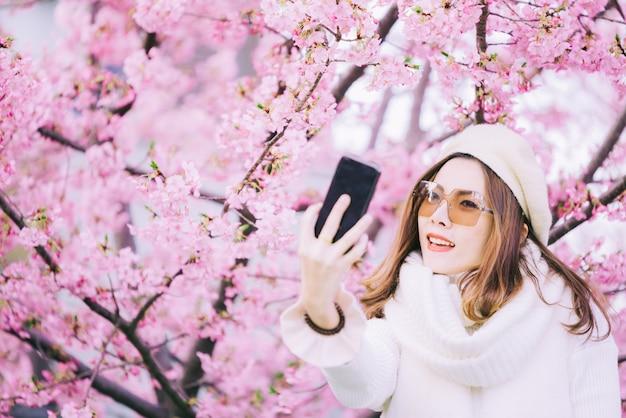 Vrouw die zelffoto in lentetijd met kersenbloesems nemen, sakura in japan
