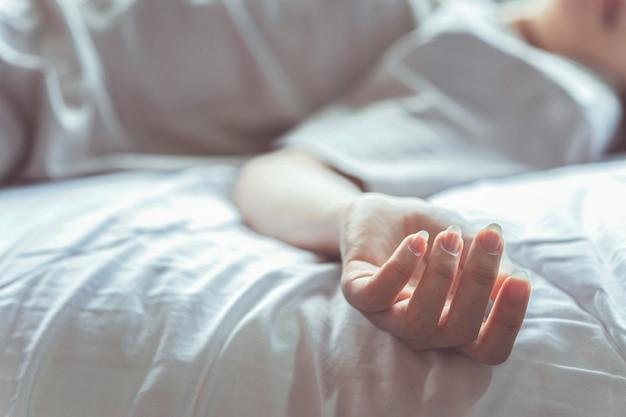 Vrouw die zelfmoord pleegt in bed focus op de hand van het lijk het concept van alleen sterven