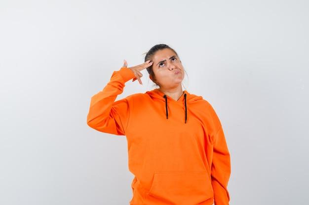 Vrouw die zelfmoordgebaar maakt in oranje hoodie en peinzend kijkt