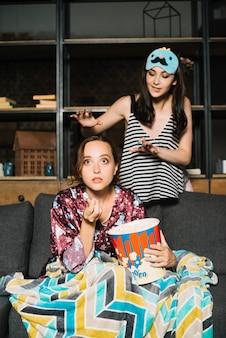 Vrouw die zich achter haar vriend het letten op televisie bevindt