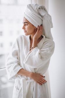 Vrouw die zich bij het raam in badjas