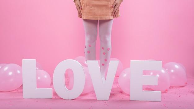 Vrouw die zich dichtbij de inschrijving en de ballons van de liefde bevindt