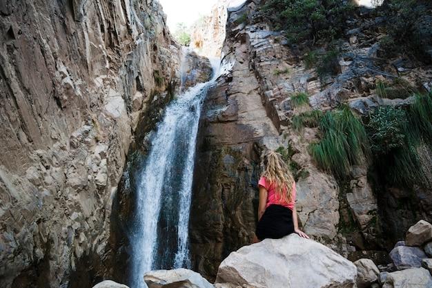 Vrouw die zich dichtbij waterval bevindt