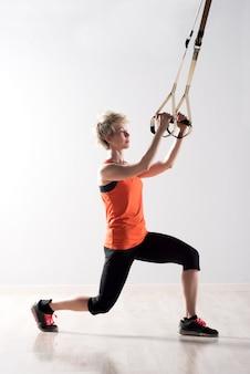 Vrouw die zich en op oefeningsringen uitrekt trekt