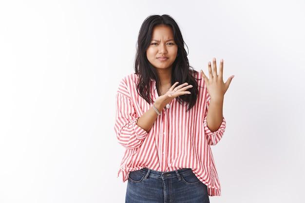 Vrouw die zich gefrustreerd en ontevreden voelt, wordt ondervraagd waar ze op valentijnsdag wachtte, handpalm tonend zonder ring en verward en geïrriteerd naar de arm wijzend, loensend, fronsend