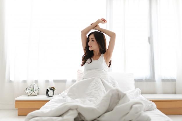 Vrouw die zich gelukkig en ontspannen na wakker in de ochtend thuis
