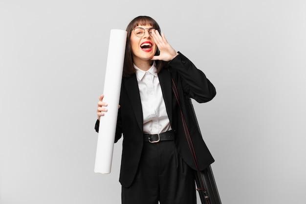 Vrouw die zich gelukkig, opgewonden en positief voelt, een grote schreeuw geeft met de handen naast de mond, roept,