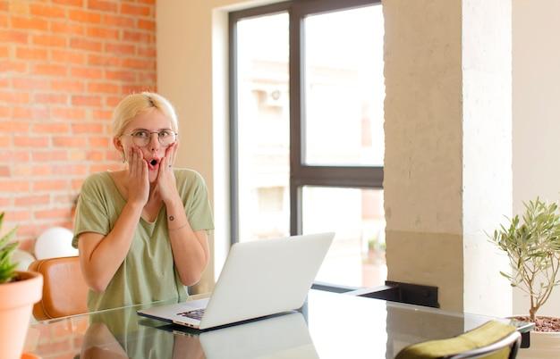 Vrouw die zich geschokt en bang voelt, vrouw die er doodsbang uitziet met open mond en handen op de wangen Premium Foto