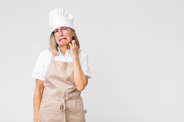 Vrouw die zich gestrest, gefrustreerd en moe voelt, pijnlijke nek wrijft, met een bezorgde, verontruste blik