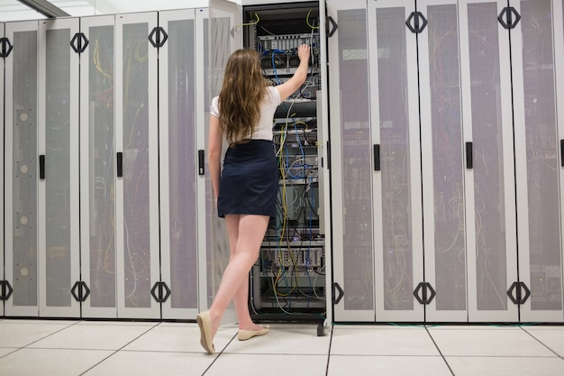 Vrouw die zich in de gang en de bevestigende draden in gegevenscentrum bevindt