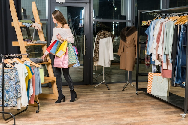 Vrouw die zich in de holdingsdocument van de kledingstellingsopslag zakken bevindt