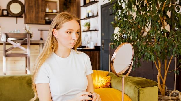 Vrouw die zich klaarmaakt om make-up te doen, kijkt naar zichzelf in de spiegel. niet blij met haar spiegelbeeld.