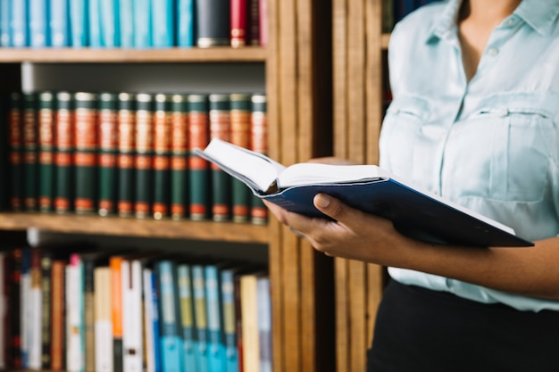 Vrouw die zich met boek in bibliotheek bevindt