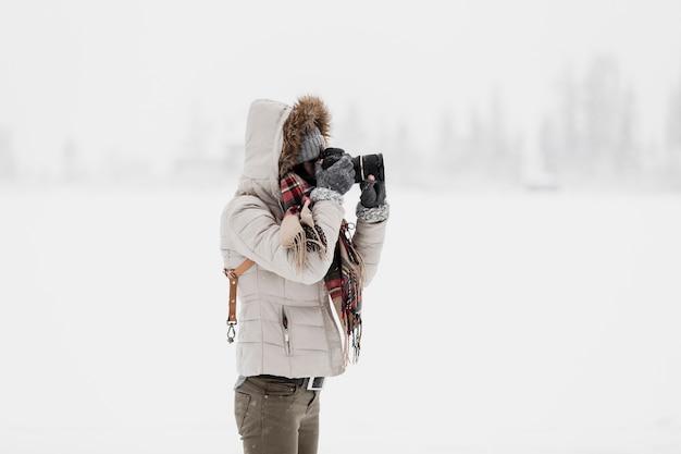Vrouw die zich met camera in de winteraard concentreert