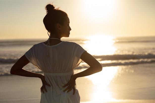 Vrouw die zich met handen op heupen op het strand bevindt