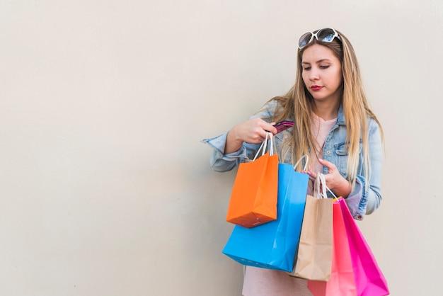 Vrouw die zich met het winkelen zakken bij muur bevindt