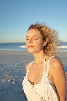 Vrouw die zich met ogen bevindt die op het strand worden gesloten