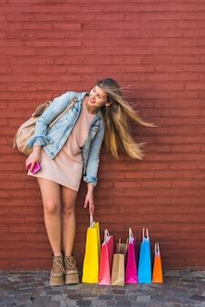 Vrouw die zich met vele het winkelen zakken bevindt bij muur