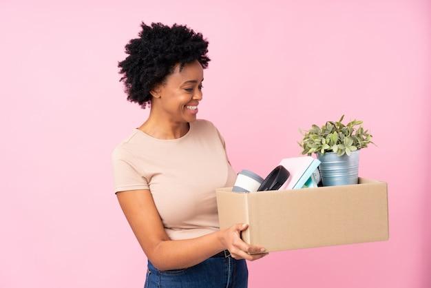 Vrouw die zich naar een nieuw huis over roze muur beweegt