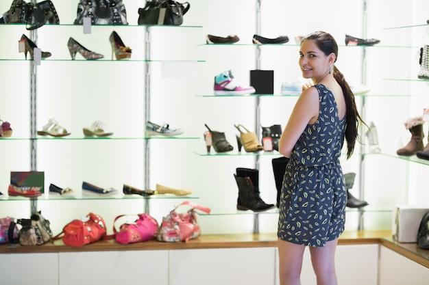 Vrouw die zich naast schoenvertoning bevindt