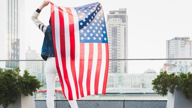 Vrouw die zich op balkon met grote amerikaanse vlag bevindt