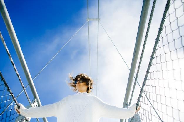 Vrouw die zich op brug hoog in hemel bevindt