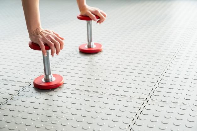 Vrouw die zich op de gewichten bevinden die van de domooroefening zich op de vloer in gymnastiek bevinden