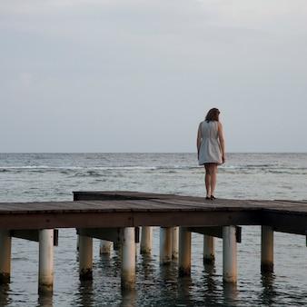 Vrouw die zich op een pijler bevindt en op zee, utila eiland, baaieilanden, honduras kijkt