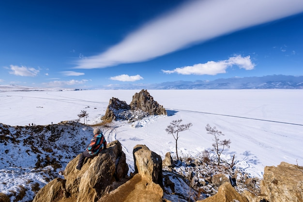 Vrouw die zich op een rots op shamanka-rots in olkhon bevindt