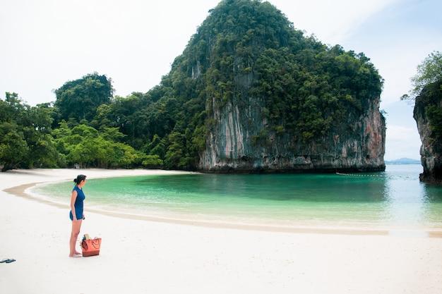 Vrouw die zich op het strand bevindt dat het overzees met strandtas en wipschakelaar op vakantie bekijkt.