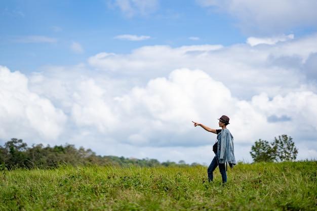 Vrouw die zich op heuvels op hemel blauwe en witte wolk bevindt