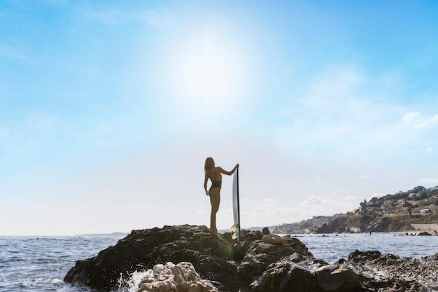 Vrouw die zich op rotsachtige kust met surfplank