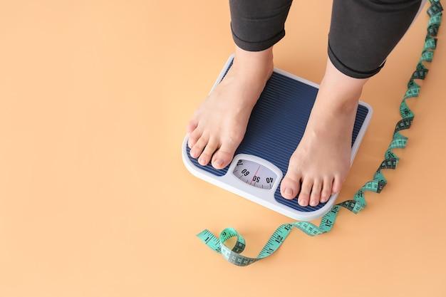 Vrouw die zich op schalen bevindt. gewichtsverlies concept