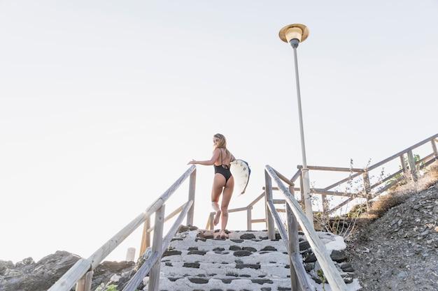 Vrouw die zich op treden met surfplank bevindt