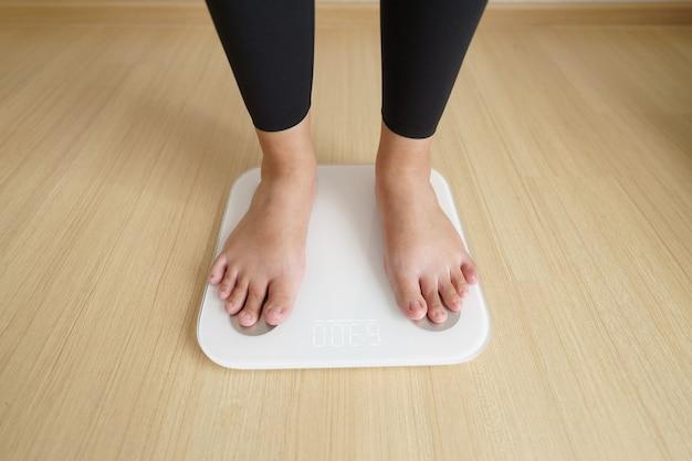 Vrouw die zich op weegt elektronische weegschaal voor het controleren van het gewicht.